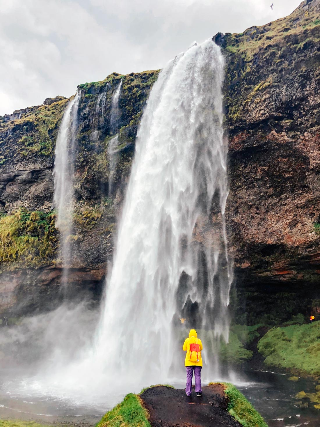 Woman in a yellow raincoat standing in front of the Seljalandsfoss waterfall