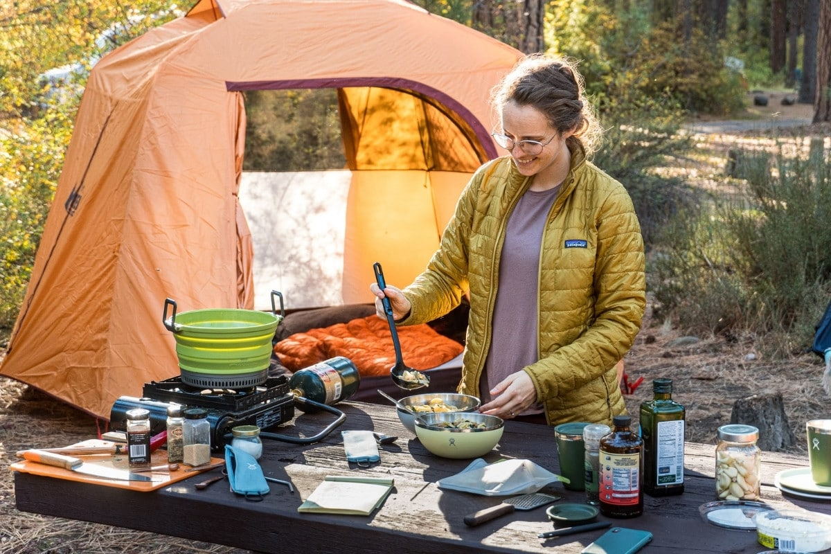 Megan ladling tortellini soup into bowls. A camp scene is in the background