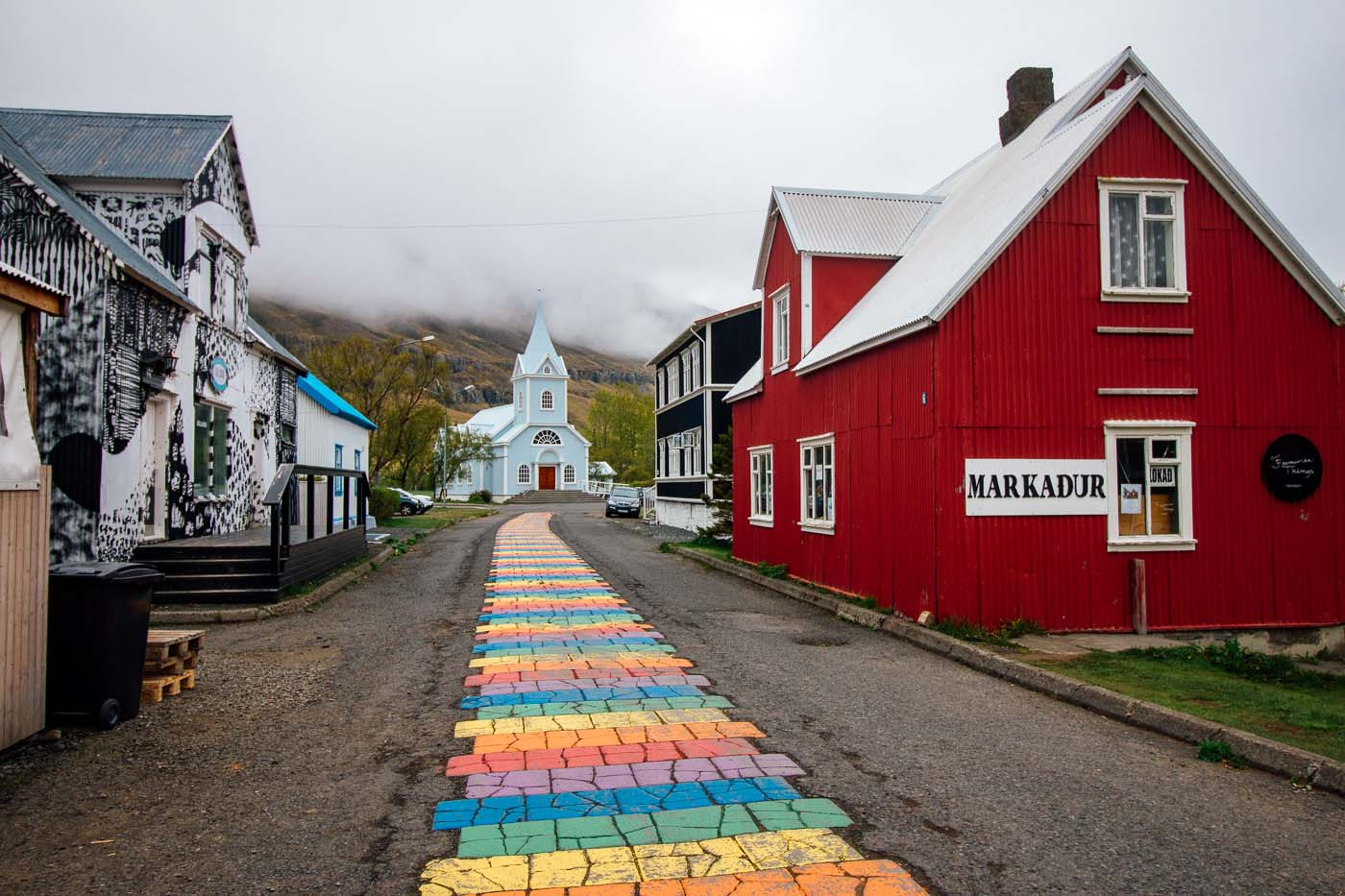 Painted rainbow road leading to a blue church