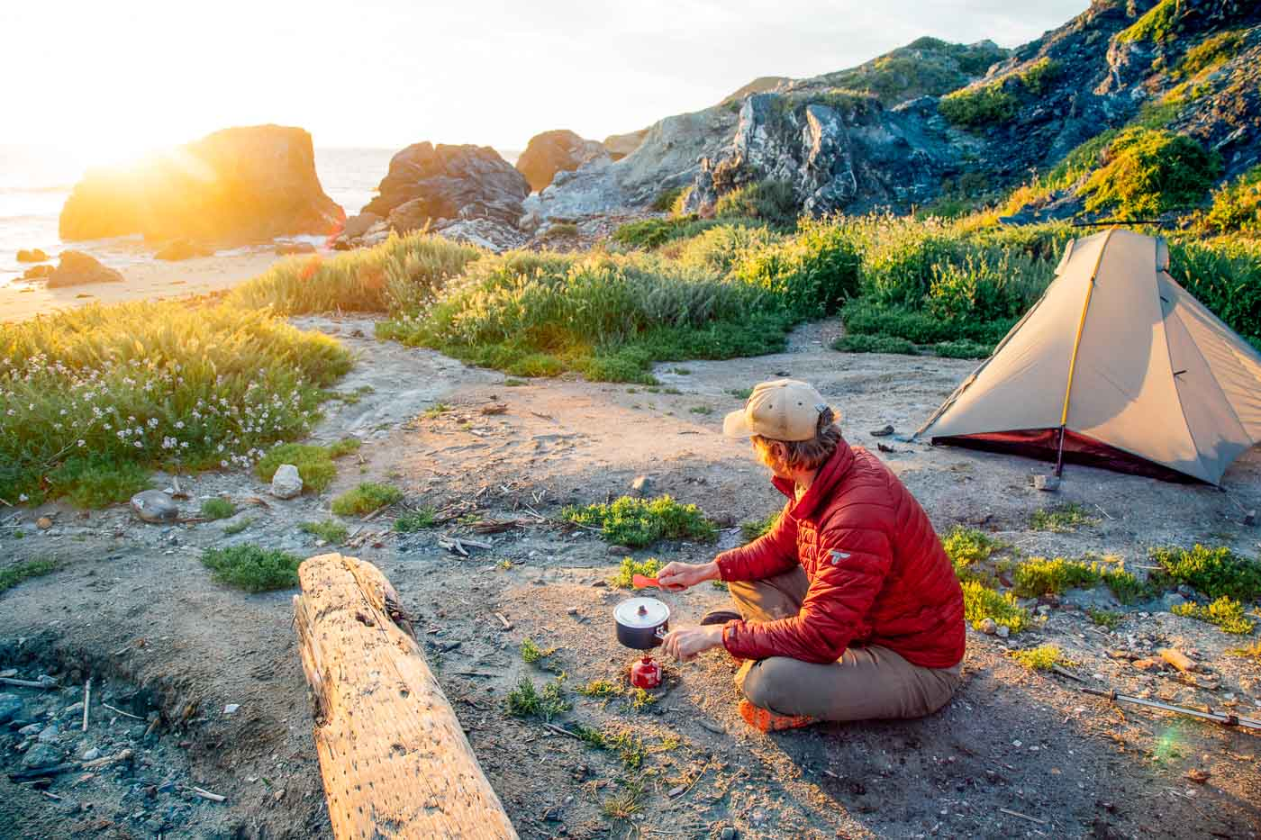 Man cooking over a backpacking stove on the beach