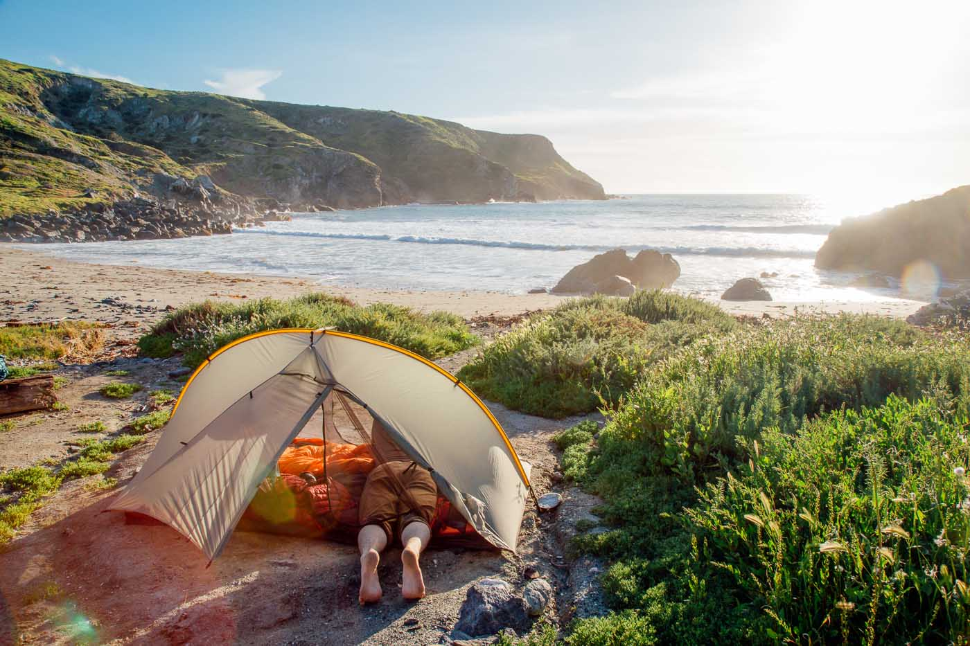 Man in a tent on the beach in Shark Harbor, Catalina Island