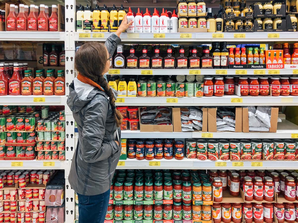 Woman selecting a bottle off a shelf at a Bonus grocery store