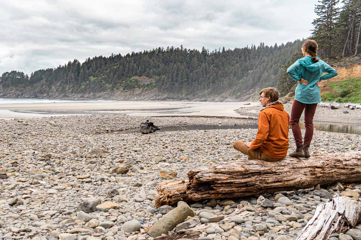 Michael is sitting on a log and Megan stands on the log next to him. They are looking out at a rocky beach.