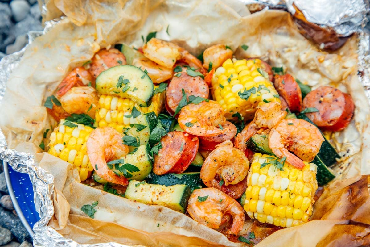 Close up of shrimp, corn on the cob, and sausage cooked in a foil packet