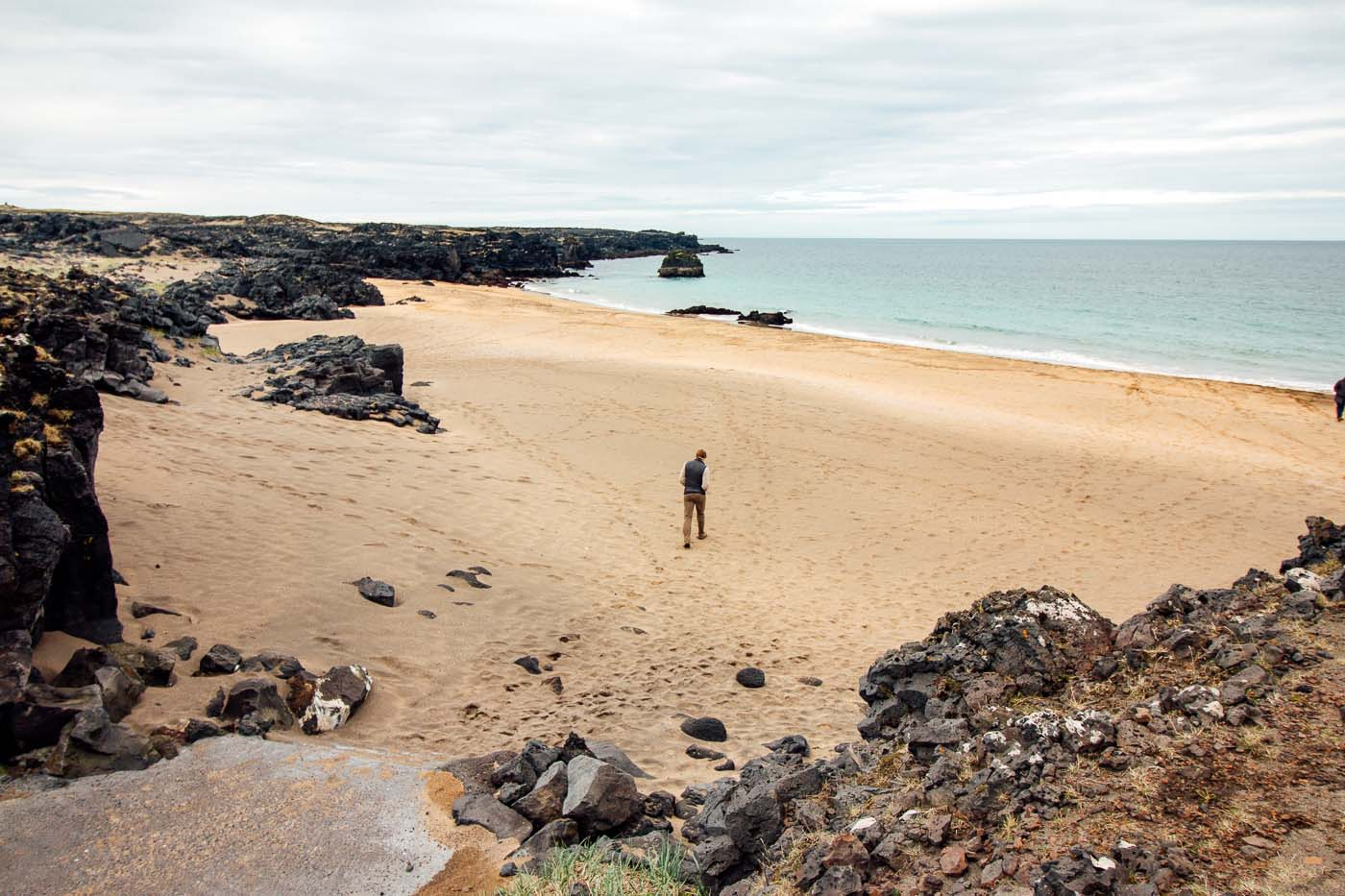 A man walking across a gold sand beach on Iceland's Snaefellsnes Peninsula