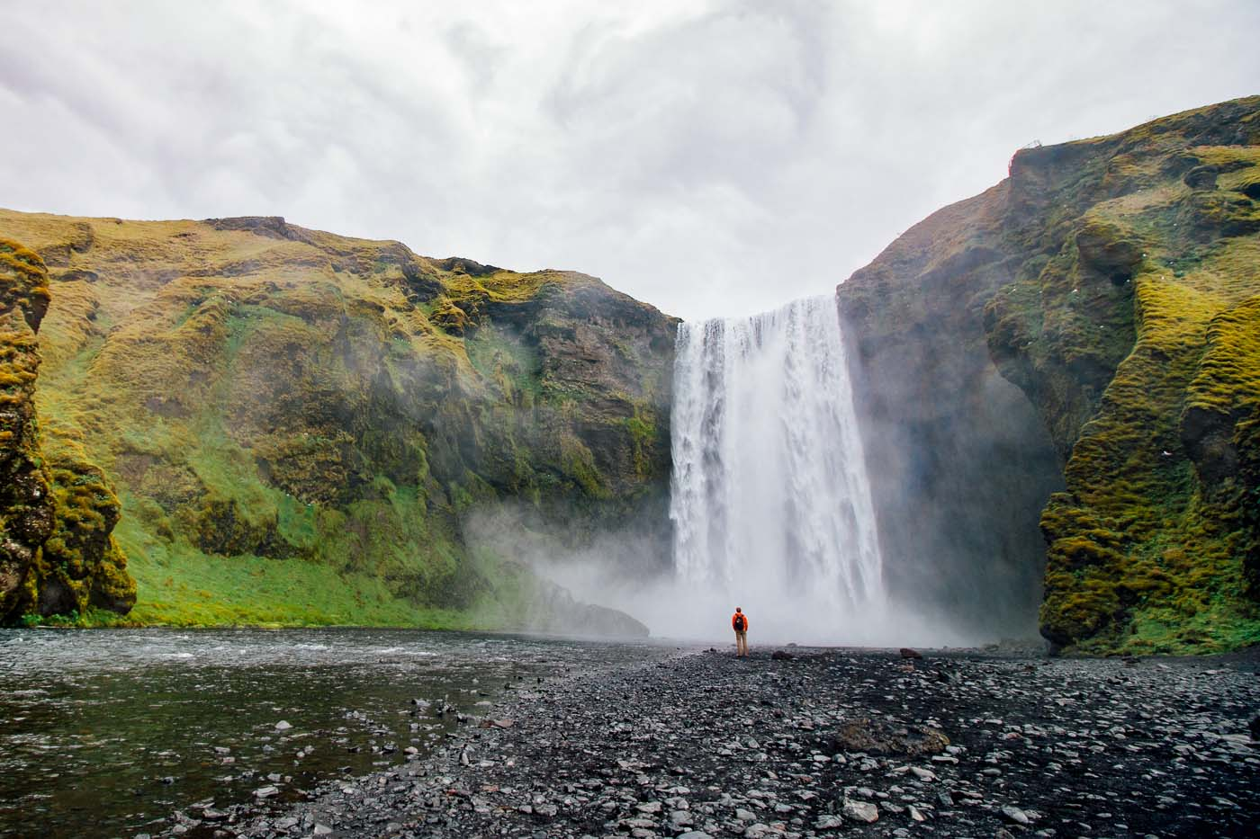 Man in an orange raincoat standing in front of the Skógafoss waterfall