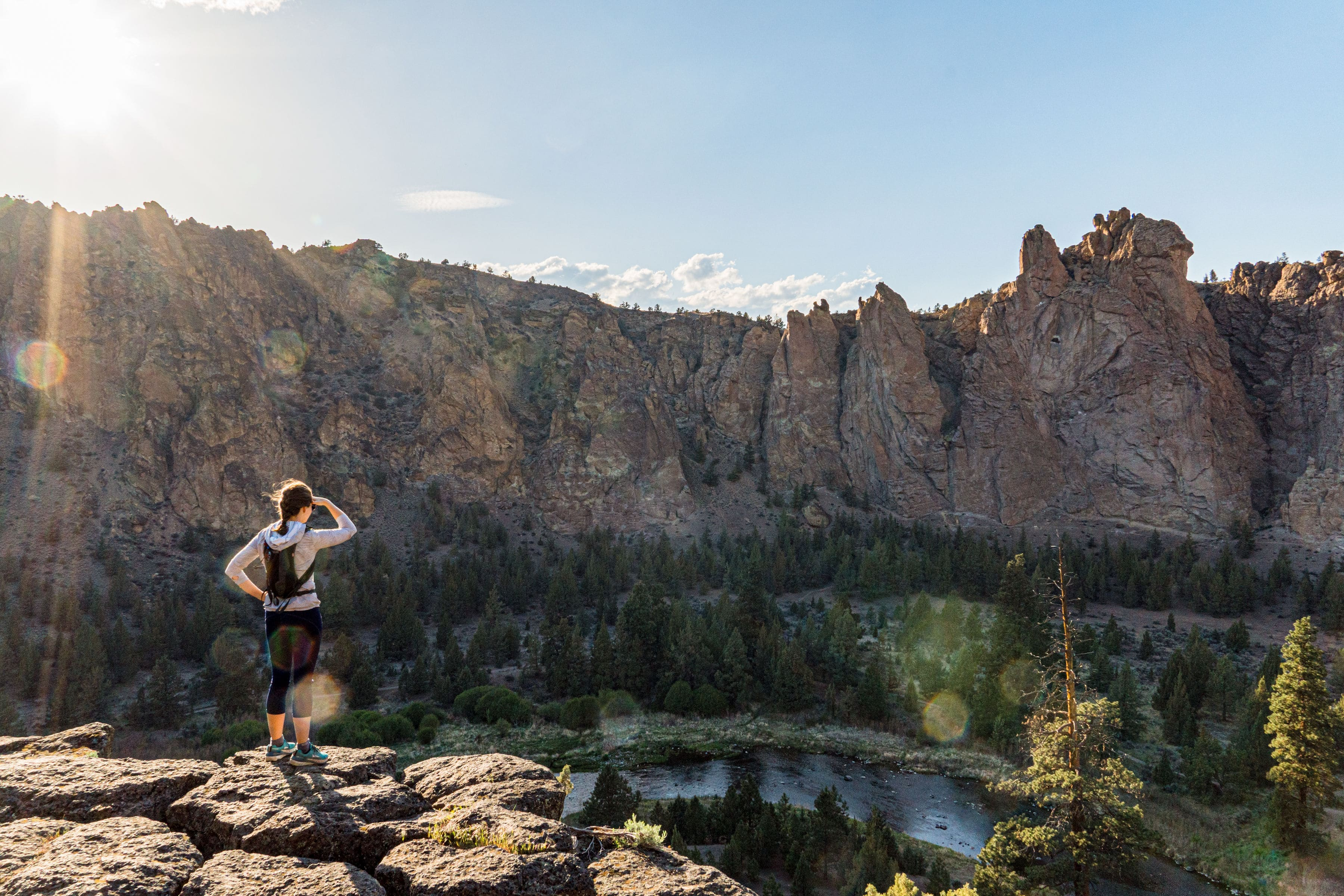 Megan standing at the edge of a trail overlooking a river and canyon walls