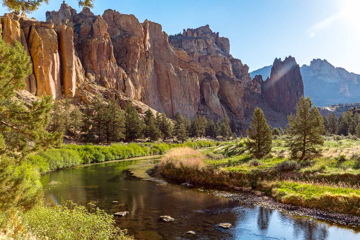The Crooked River running through the canyon at Smith Rock State Park. Orange and red rocks make up the canyon walls.