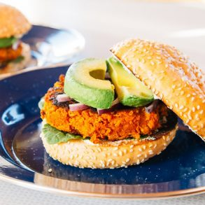 Sweet potato bean burger topped with avocado on a blue blate