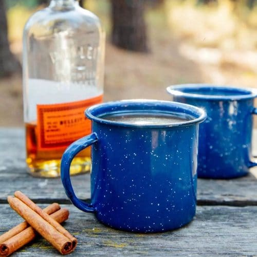 A blue enamel mug next to a bottle of whiskey