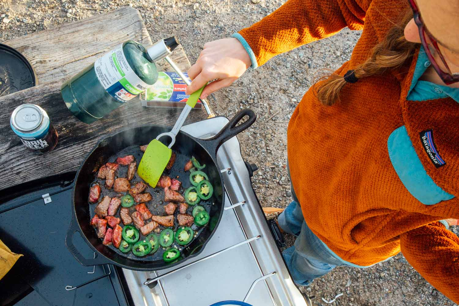 Overhead shot of a woman cooking steak and jalapeños in a cast iron skillet over a camping stove.