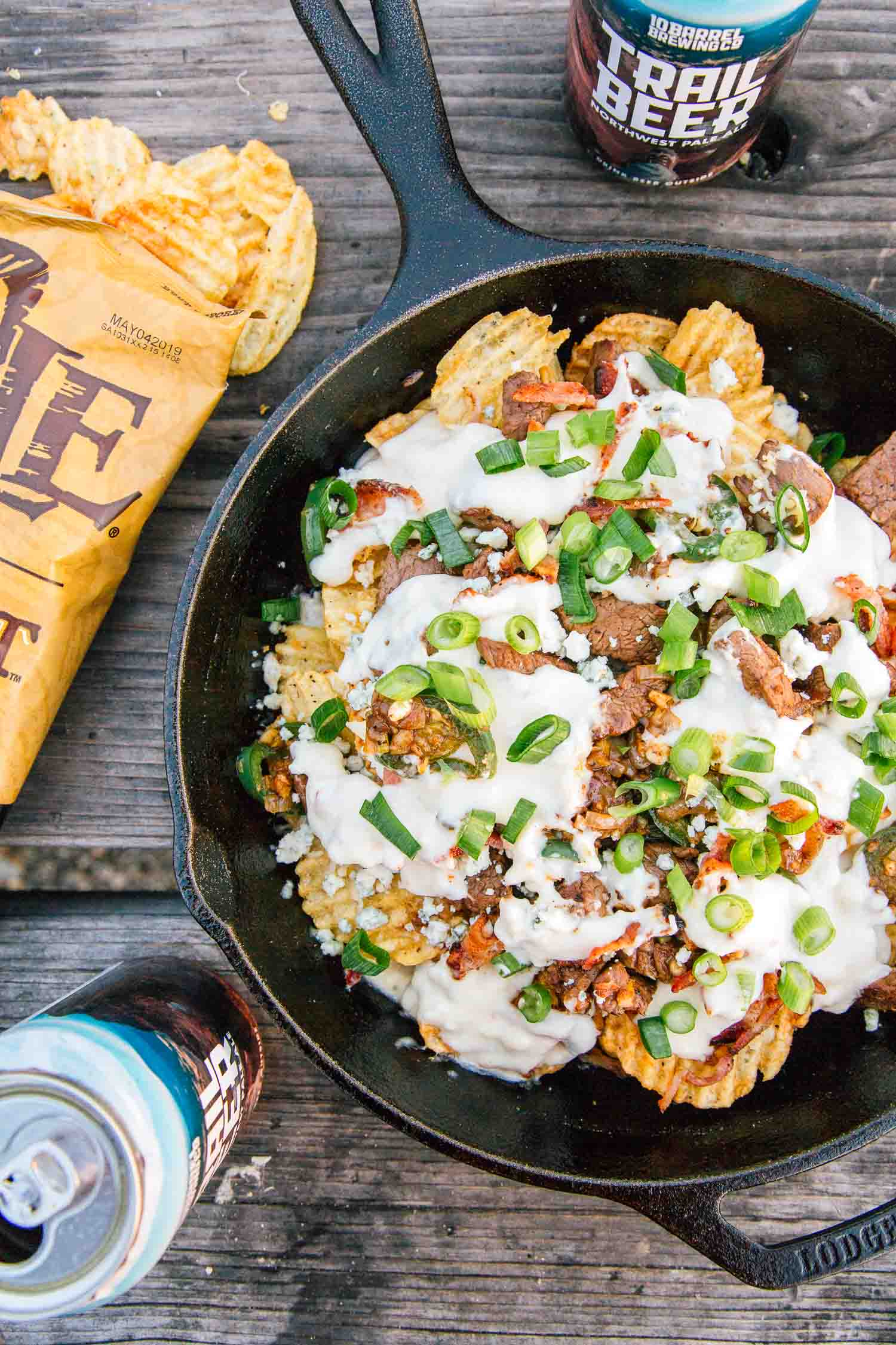Overhead shot of cast iron skillet nachos. A bag of chips and a can of beer are in frame.
