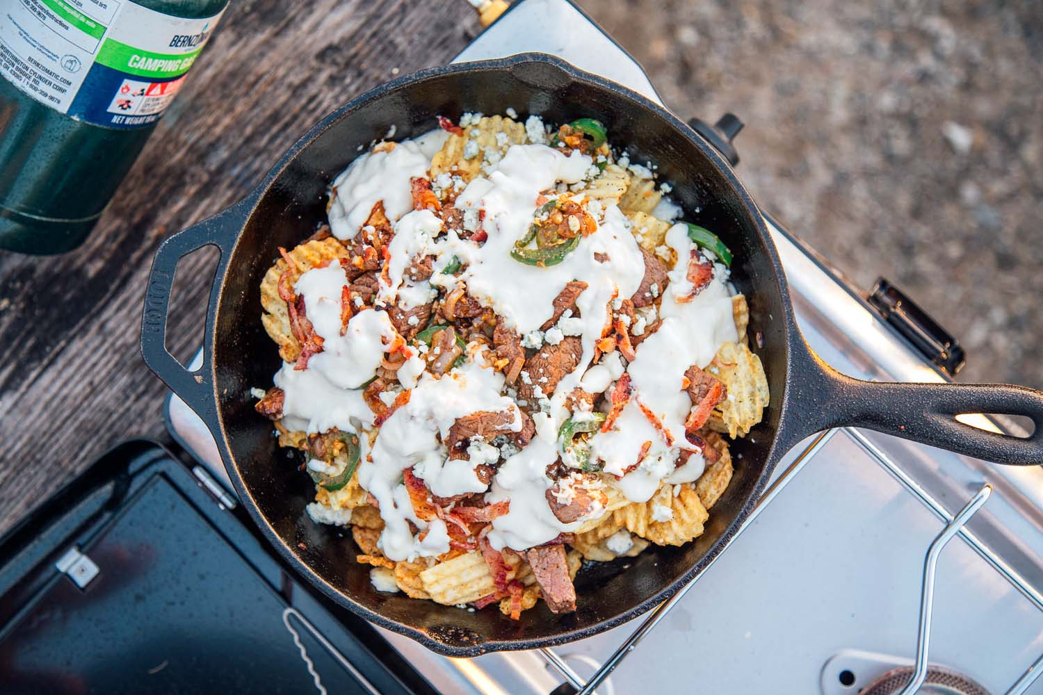 Overhead shot of nachos in a cast iron skillet on a camping stove.