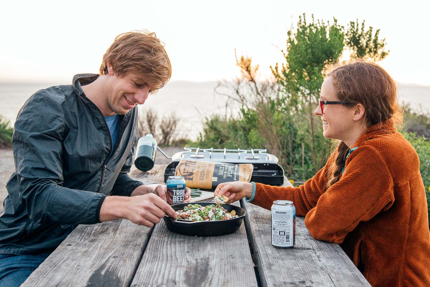 Man and woman sitting at a picnic table sharing a plate of nachos at a camp site with bushes in the background.