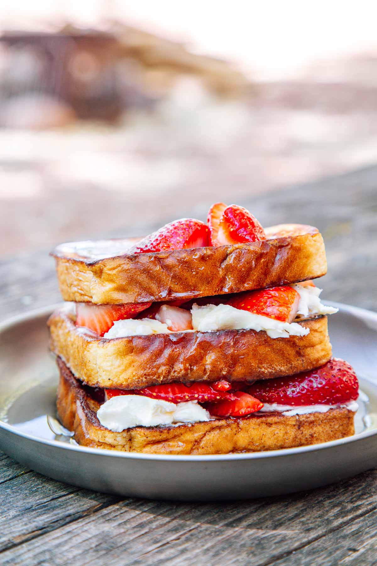 Stuffed french toast topped with strawberries on a camping plate