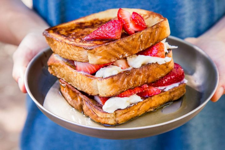 Michael holding a plate of stuffed french toast topped with strawberries