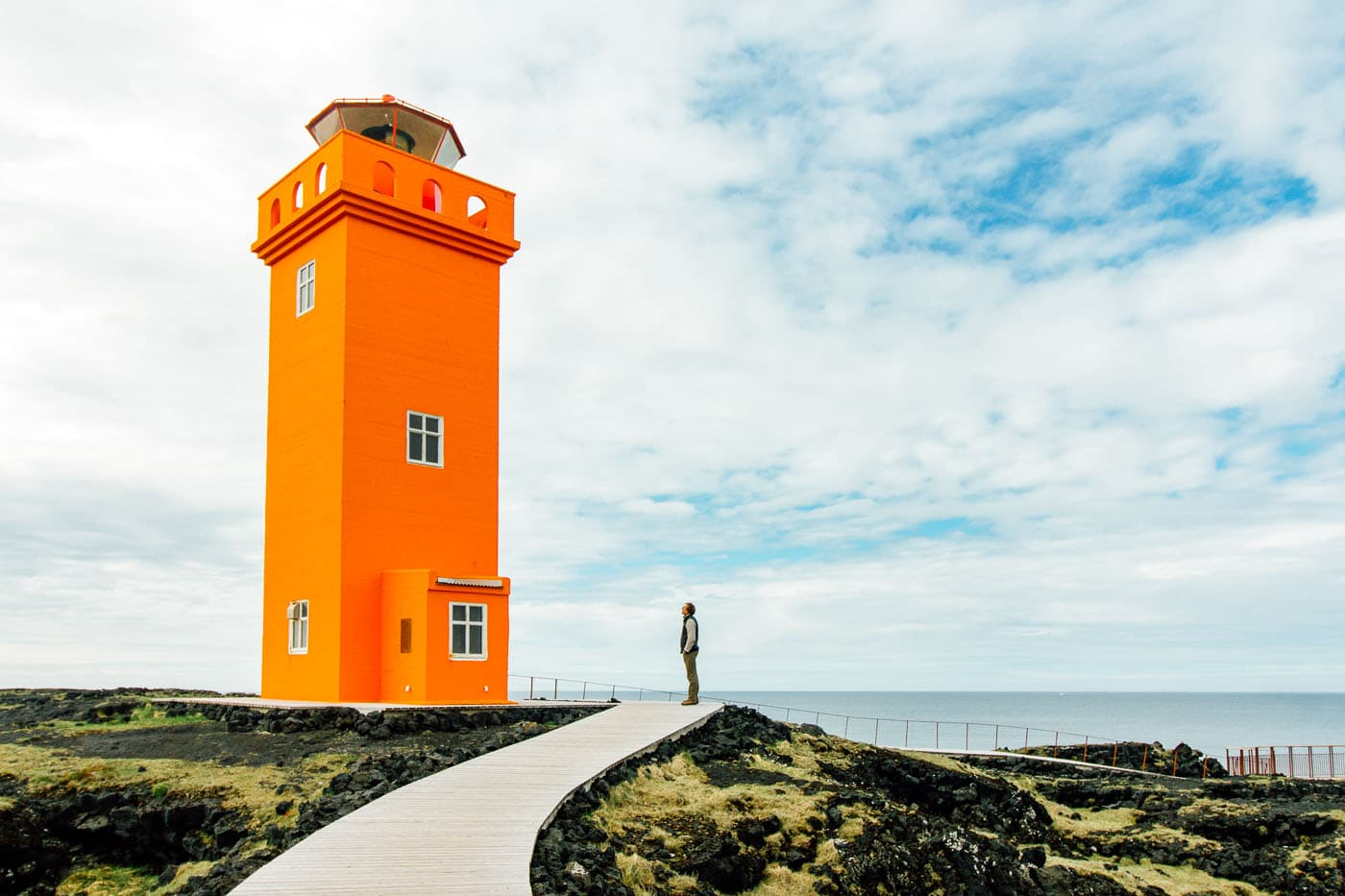Man looking up at a towering orange lighthouse with blue skies in the background