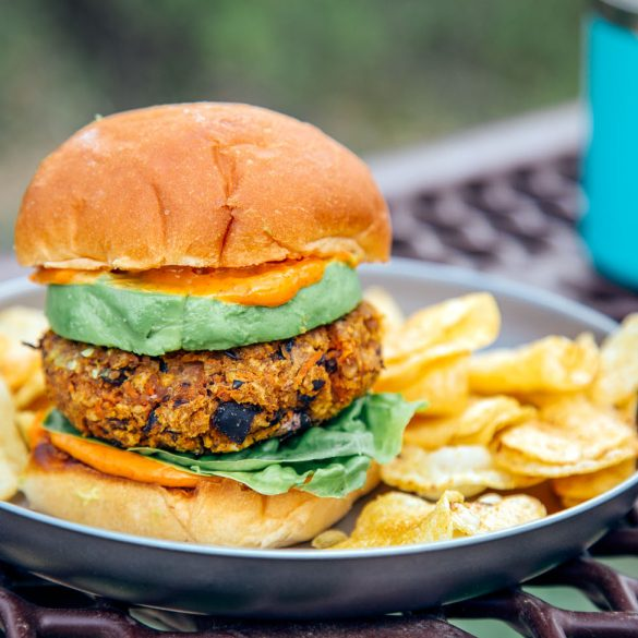 A sweet potato black bean burger stacked between two buns, avocado, and spicy mayo on a plate with a natural backdrop.