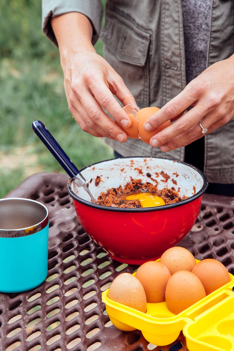 Cracking an egg into a red bowl with other black bean burger ingredients.