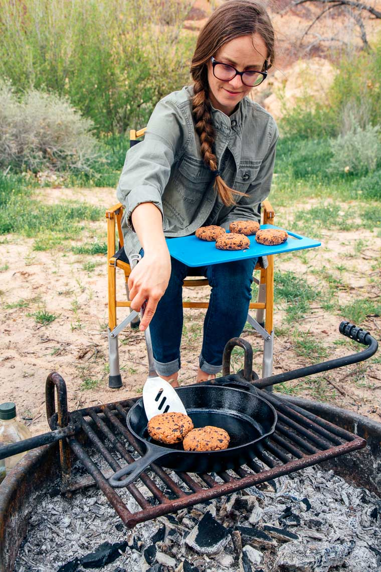 Megan is transferring black bean burger patties from a cutting board into a skillet over the campfire.