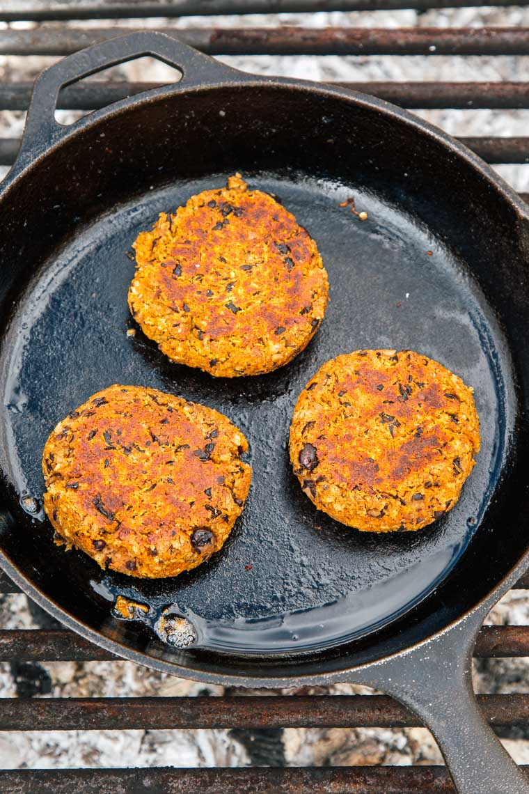 Three black bean burger patties cooking in a cast iron skillet over a campfire.