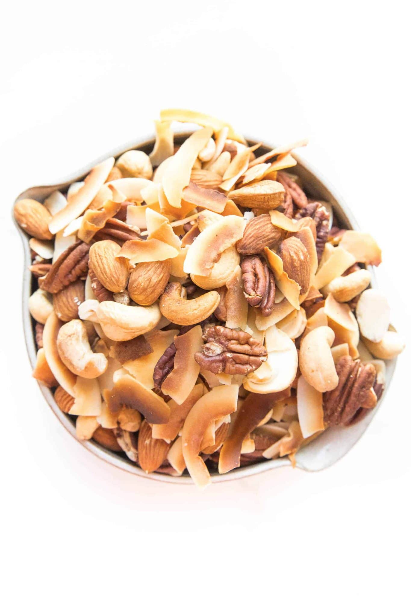 Assorted nuts and coconut chips in a bowl on a white surface