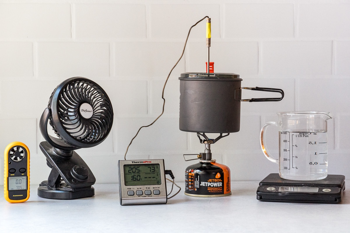 Backpacking stove testing environment including fan, stove and pot, thermometer, scale, and anemometer
