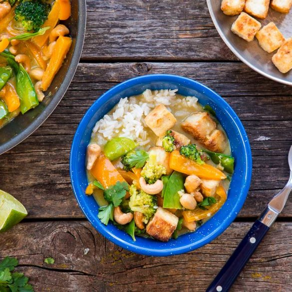 A blue bowl filled with Thai green curry on a wooden camping table