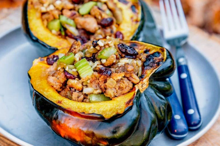 Acorn squash halves filled with stuffing on plates with fall foliage in the background