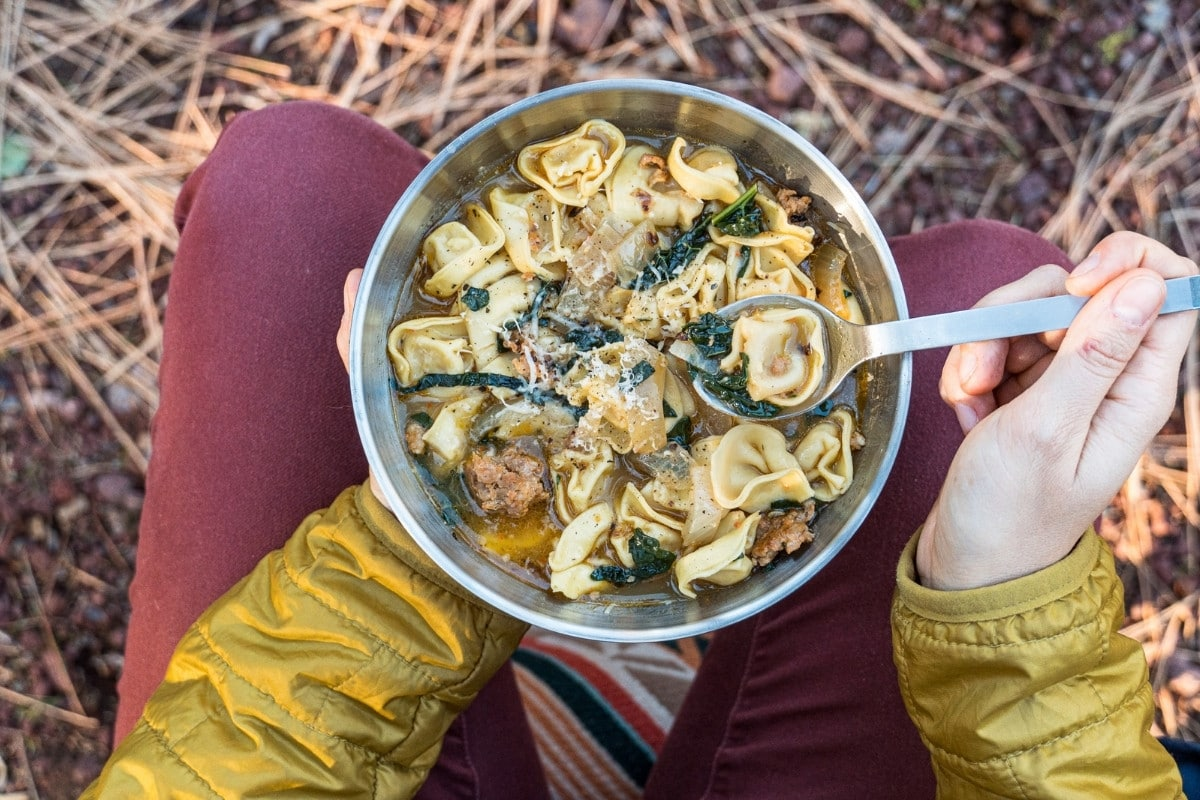 Overhead view of Megan holding a bowl of tortellini soup