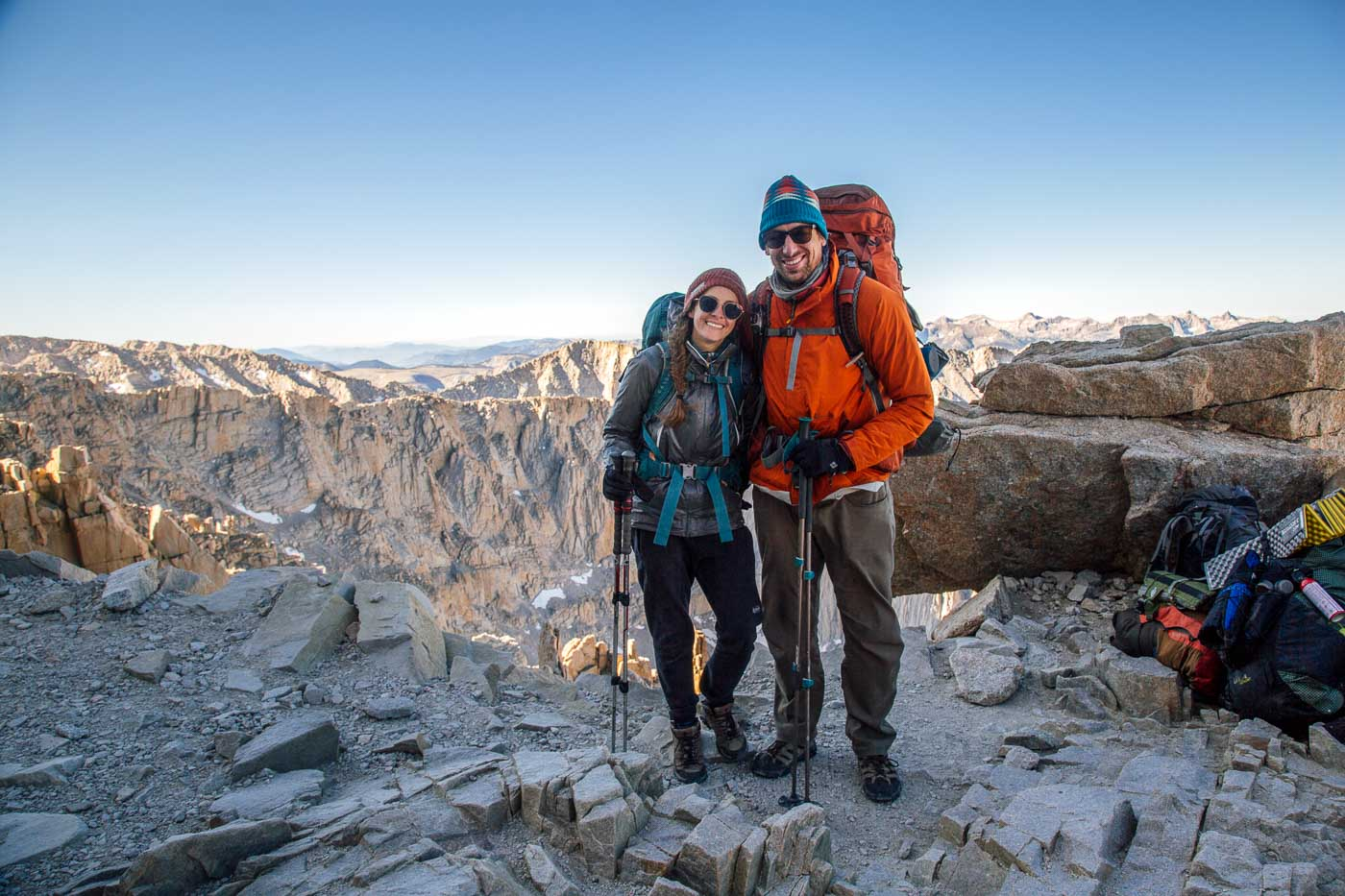 Megan and Michael wearing backpacking packs in the mountains