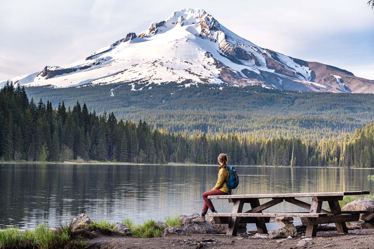 Megan is sitting on a picnic table on the shores of Trillium Lake. Her head is turned and she is looking at Mt. Hood.