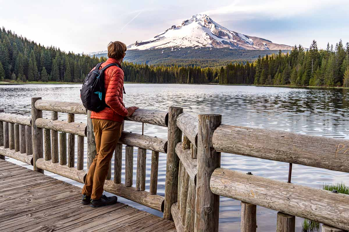 Michael stands on a rustic wooden boardwalk. He is looking out at a lake with a view of Mt. Hood in the distance.