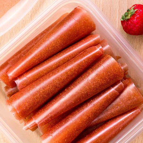 Fruit leathers rolled up and stacked in a tupperware container.