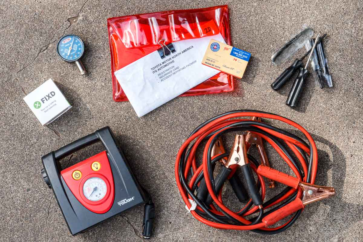 Overhead view of jumper cables, tire patch kit, tire pressure guage, and a tire inflator