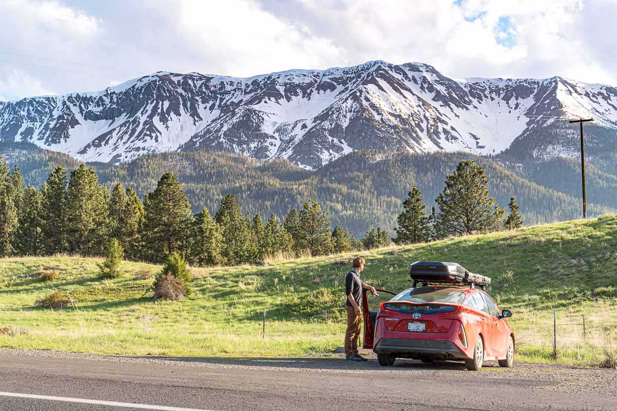 Michael standing next to a red Prius Prime with the Wallowa Mountains in the distance.