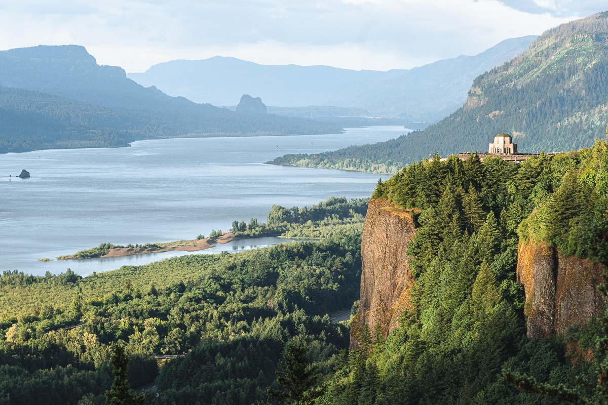A view down the Columbia River Gorge. The Vista House sits on a rocky bluff.