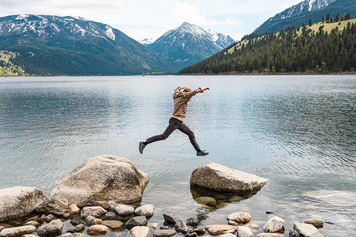 Michael hops between two boulders in Wallowa Lake with the Wallowa Mountains in the background