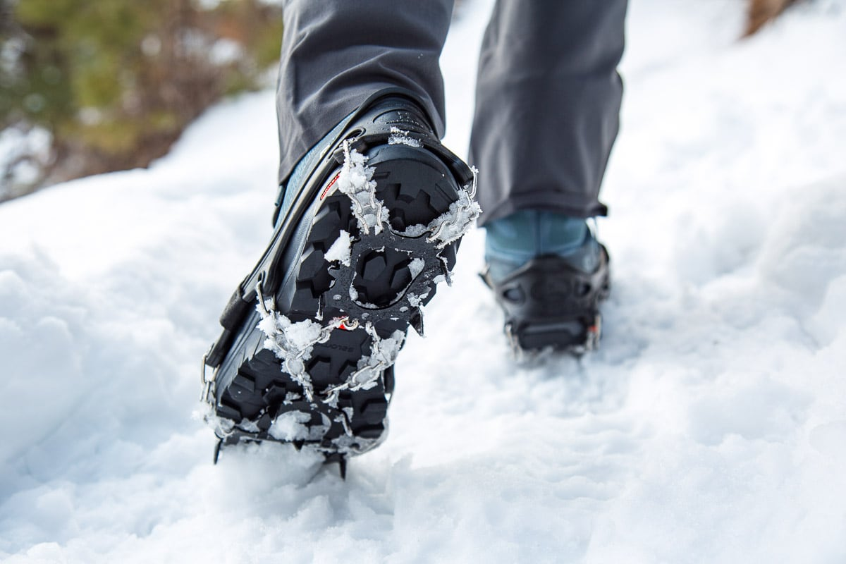 Megan walking with trail crampons attached to a pair of winter hiking boots.