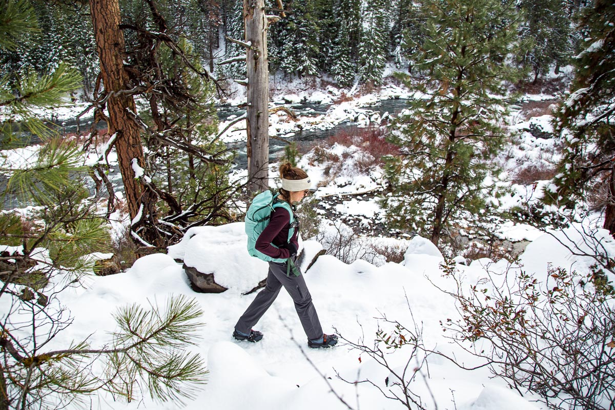 Megan hiking on a snowy trail. She is wearing a wool baselayer top and winter hiking pants.