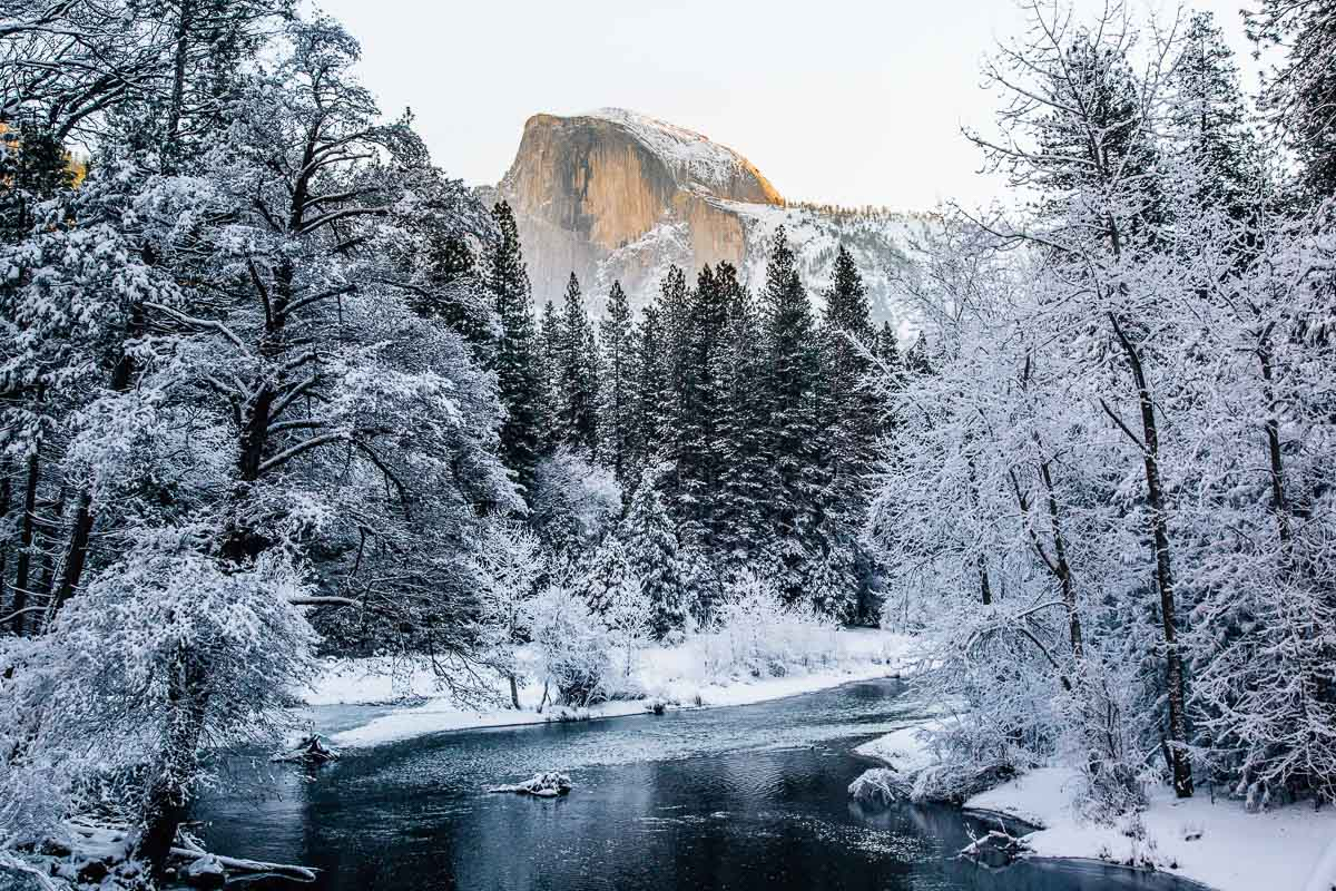 Half Dome covered in snow as seen over the Merced River in Yosemite Valley