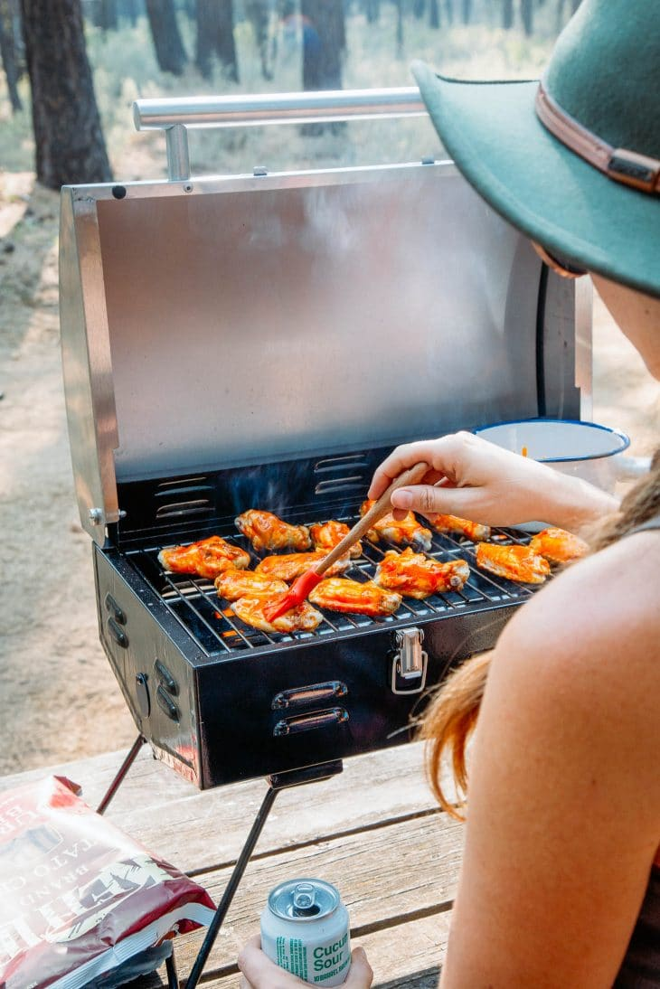 Megan basting wings on a grill with hot sauce