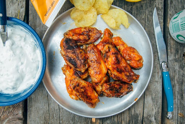 Grilled buffalo wings on a plate with potato chips
