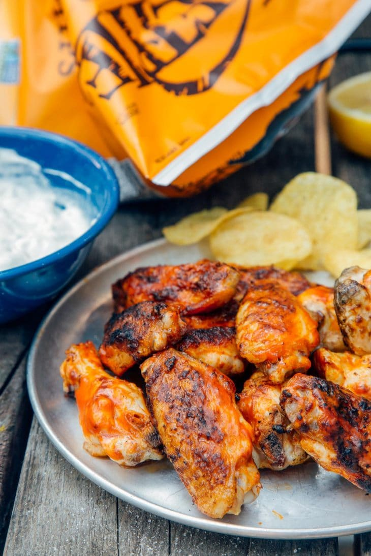 Grilled buffalo wings on a silver plate with potato chips