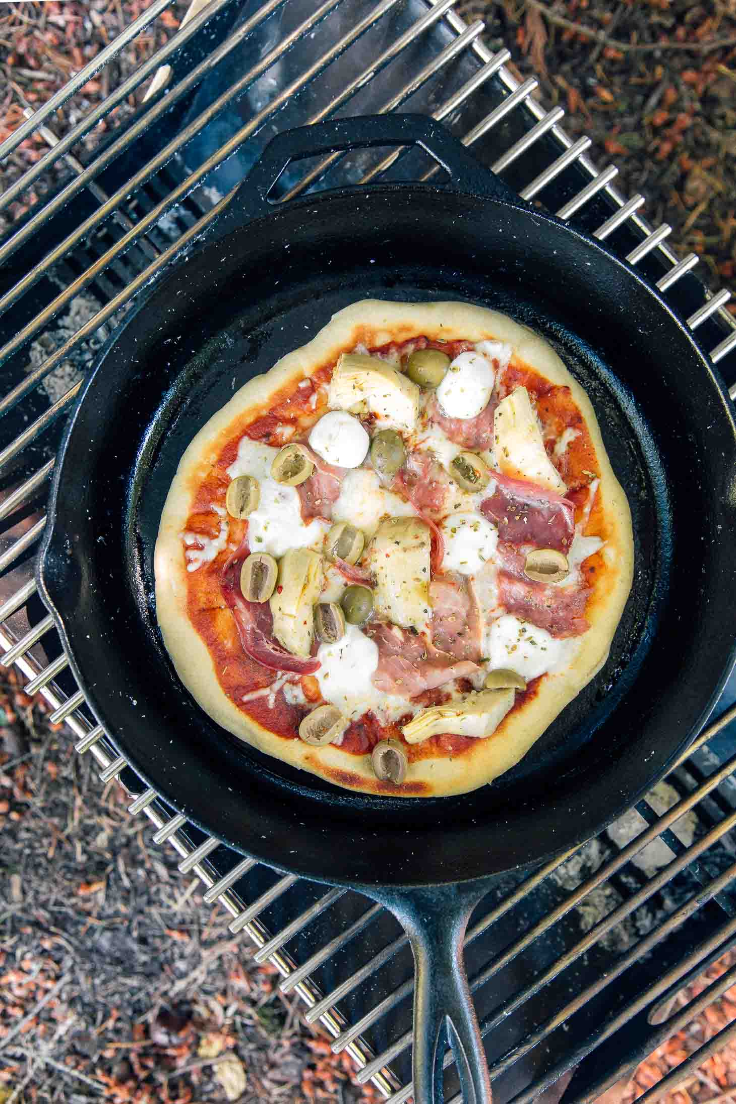 Antipasto pizza with proscuitto, artichoke hearts, olives, and mozzarella cheese in a cast iron skillet on a grill