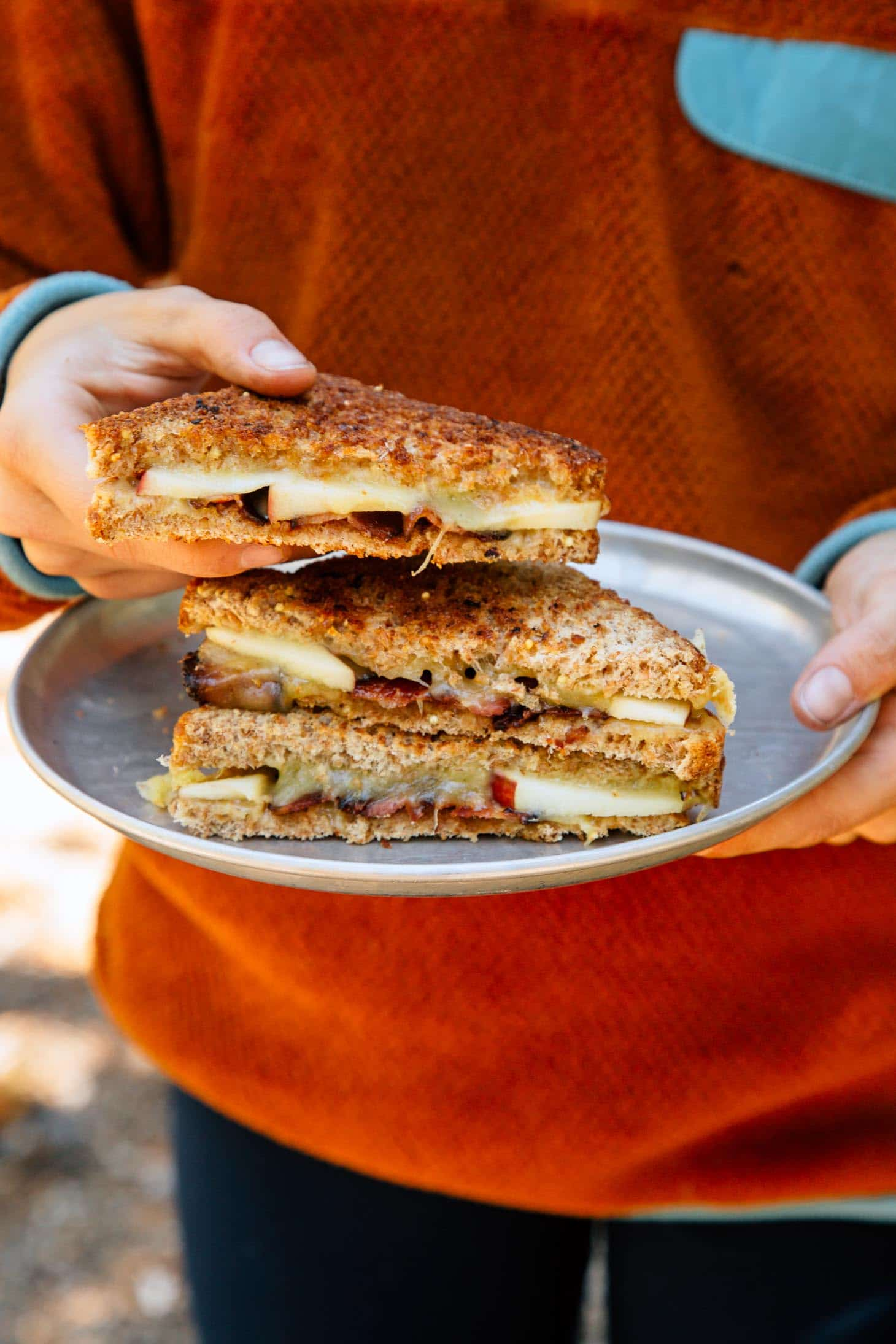 Holding an apple cheddar grilled cheese sandwich.