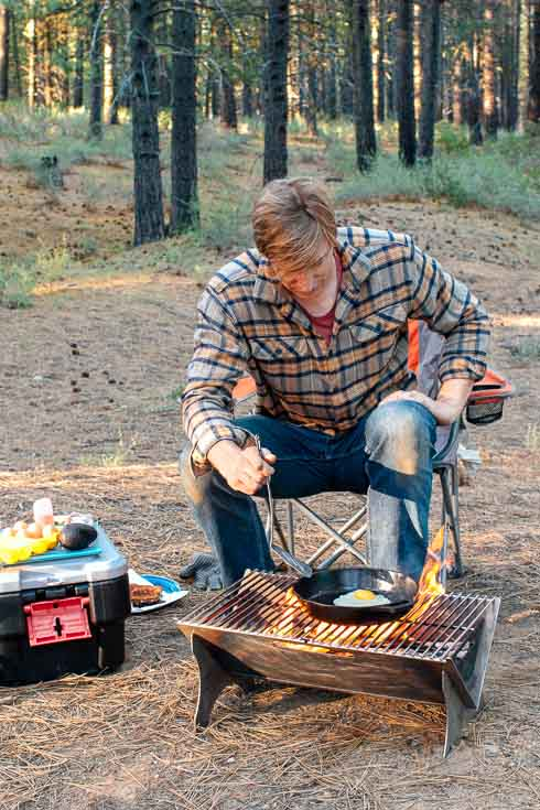 Man sitting next to a campfire cooking an egg in a cast iron skillet