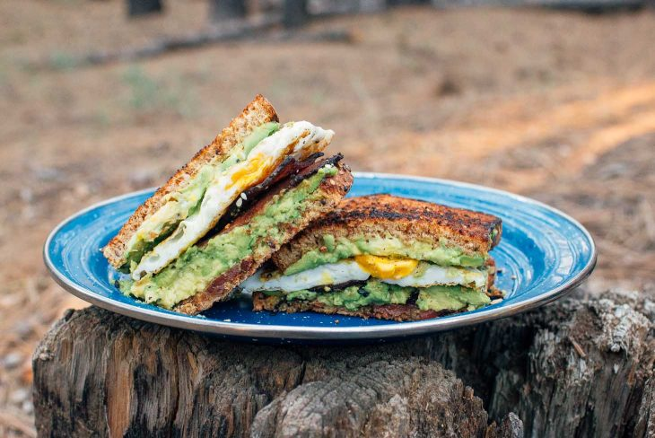 Breakfast sandwich with avocado, egg, and bacon on a blue camping plate placed on a log