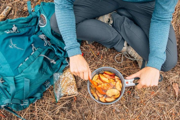 Megan sitting on the ground cooking an apple crisp in a backpacking pot.