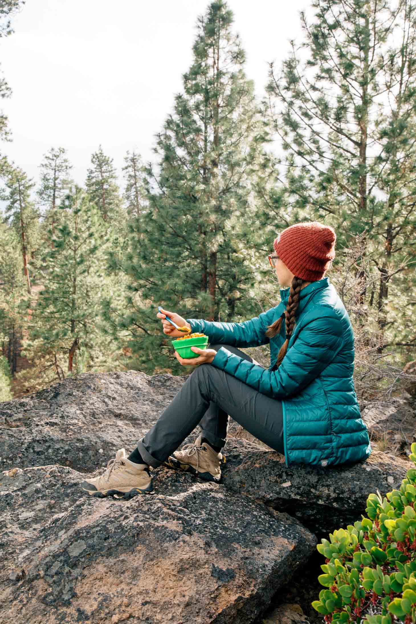 Megan sitting on a rock in the forest holding a green bowl